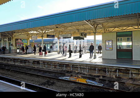 People waiting for a train standing on the platform at Cardiff Central Railway Station in Cardiff Wales UK  KATHY - Stock Photo