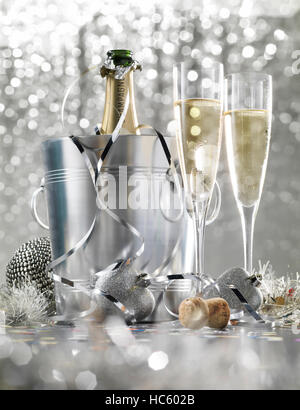 Two glasses of champagne with bottle in cooler on a silver bokeh background - Stock Photo