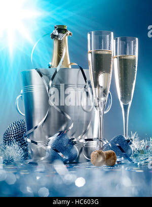 Two glasses and a cooler of champagne on bright blue background - Stock Photo