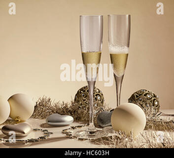 Two glasses with champange, gift boxes and christmas decorations on a yellow background with lights of garland. - Stock Photo