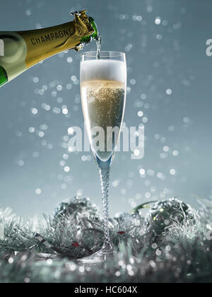 pouring champagne into the glass on a blue christmas background - Stock Photo