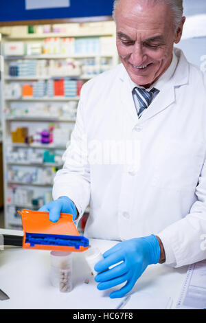 Pharmacist putting pills in container - Stock Photo
