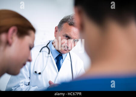 Thoughtful doctor standing with surgeons in corridor - Stock Photo