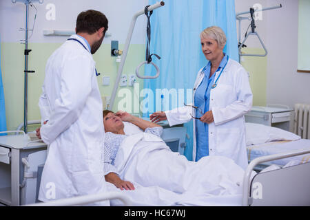 Doctors talking to a senior patient - Stock Photo