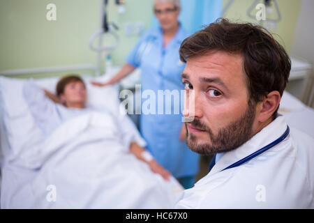 Portrait of doctor standing in hospital room - Stock Photo