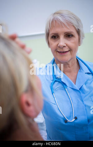 Nurse checking patient temperature - Stock Photo