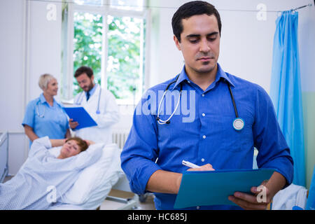 Doctor checking a medical report - Stock Photo