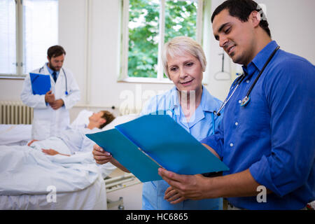 Doctor and nurse checking a medical report - Stock Photo
