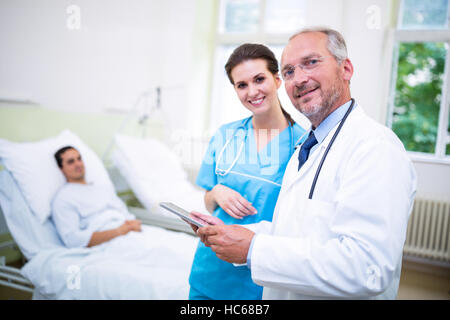 Doctor and nurse discussing on digital tablet - Stock Photo