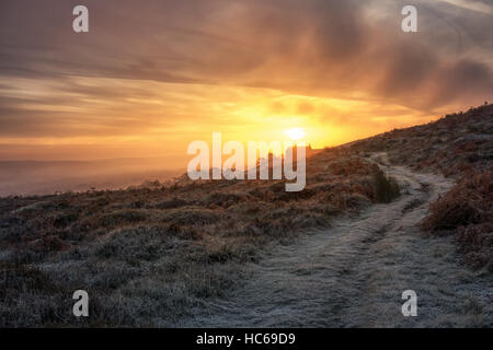 Winter ramble on frosty path: Rural house on a hill enjoying a beautiful dramatic sunrise above the mist hanging - Stock Photo
