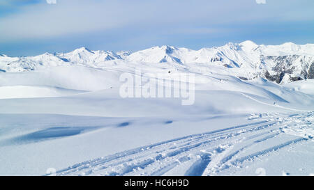 ski tracks on fresh snow in mountains with alpine peaks in the background. Winter snowy peaks landscape. - Stock Photo