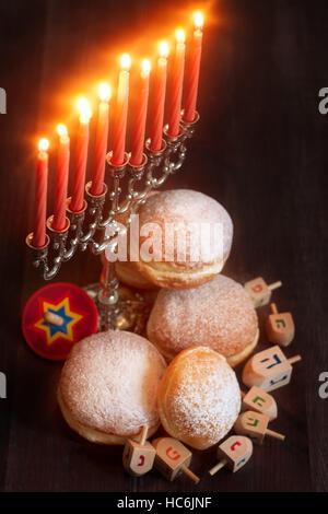 Symbols of jewish holiday hanukkah - menorah, donuts sufganiyot and dreidels - Stock Photo