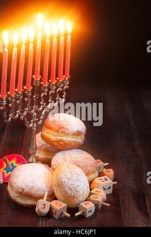 Symbols of jewish holiday hanukkah - menorah, donuts sufganiyot and dreidels. Copyspace background. - Stock Photo