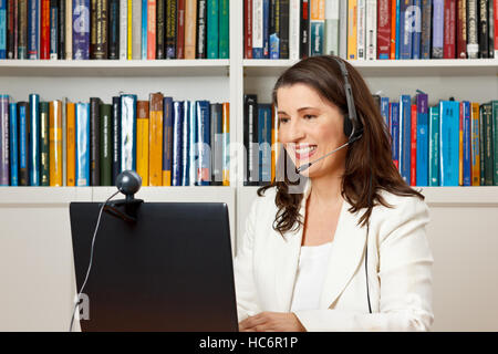 Smiling businesswoman in front of her computer in her office having a video call with her family at home, voip - Stock Photo