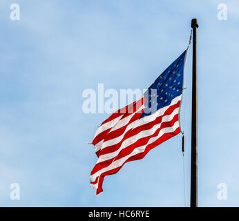American flag - the stars and stripes flying against a blue sky - Stock Photo
