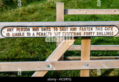 Any person who omits to shut and fasten this gate is liable to a penalty of 40 shillings - sign on a wooden field - Stock Photo