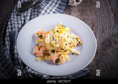 Tagliatelle with shrimps on a white plate - Stock Photo