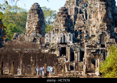 Tourists stand in front of the outer bas-reliefs at Bayon Temple, Angkor Archaeological Park, Siem Reap Province, - Stock Photo