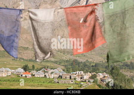 Buddhist prayer flags fluttering in the wind above the Himalayan village of Tandi along the Manali to Leh mountain - Stock Photo