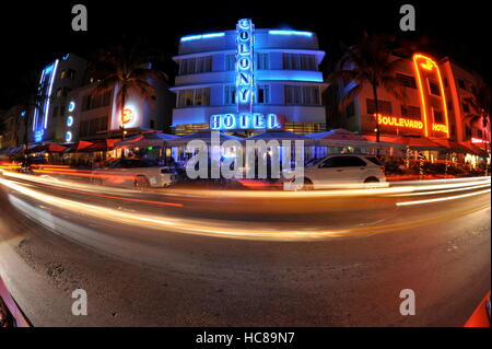 Row of art deco hotels at night with neon lights, including Colony Hotel, with vehicles blurring by with timed exposure, - Stock Photo