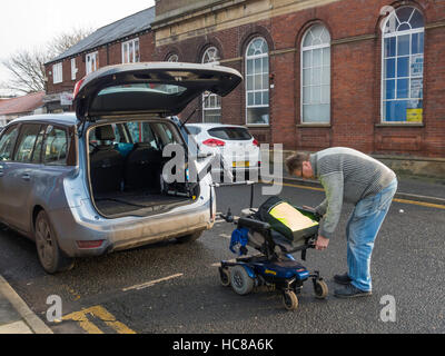 Man rigging lifting equipment on a Mobility Scooter ready to lift it into the back of an estate car using a built - Stock Photo