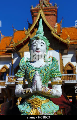 Praying statue in front of the ordination hall at Wat Buppharam Temple in Chiang Mai, Thailand - Stock Photo