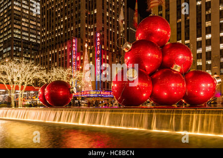 Giant red holiday ornaments on 6th Avenue. Christmas season decorations. Midtown. New York City - Stock Photo