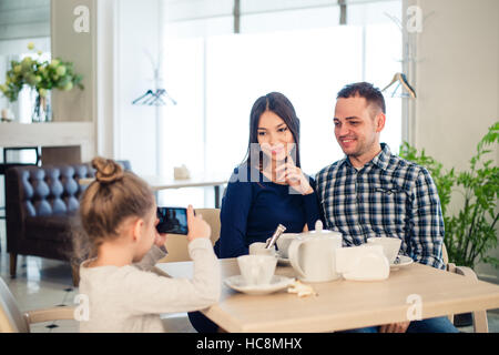 family, parenthood, technology people concept - close up of happy mother, father and little girl having dinner, - Stock Photo