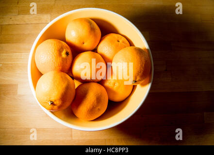 Clementine oranges in a bowl on a wooden counter - Stock Photo