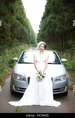 Young smiling bride standing in front of a car outdoors - Stock Photo