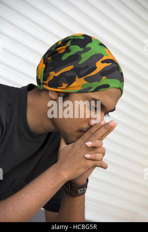 Close-up of a young Indian boy sitting in deep thought - Stock Photo