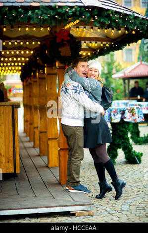 Eve of Christmas. Cute young couple has good time at the Christmas bazaar. Young people stand near wooden counter - Stock Photo
