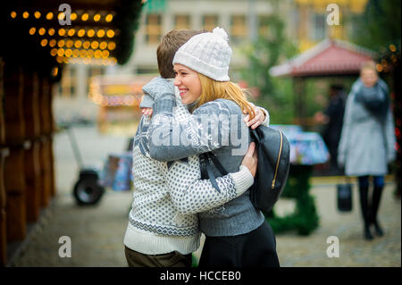 Eve of Christmas. Cute young couple has a good time at the Christmas bazaar. Young people stand in the middle of - Stock Photo