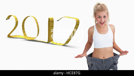 Composite image of thin woman wearing old pants after losing weight - Stock Photo