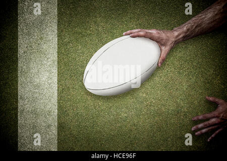 Composite image of cropped image of a man holding rugby ball - Stock Photo