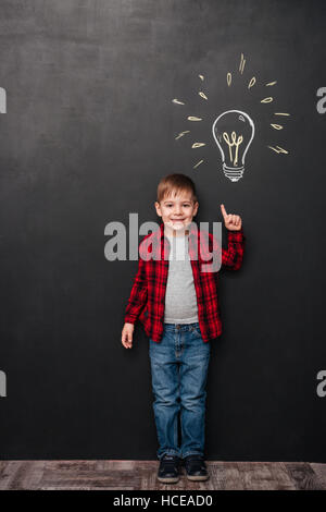 Picture of little boy pointing up and having an idea over chalkboard background with drawings. Looking at camera. - Stock Photo