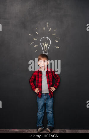Picture of a little surprised boy having an idea over chalkboard background with drawings. Look aside. - Stock Photo
