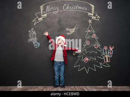 Picture of happy screaming child wearing hat standing near Christmas drawing on blackboard. Looking at camera. - Stock Photo