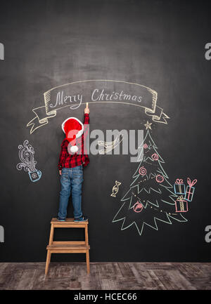 Picture of happy child wearing hat standing on stool near Christmas tree while drawing on blackboard. - Stock Photo