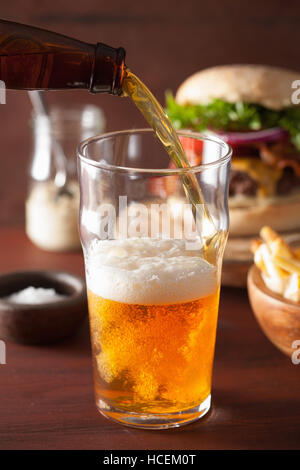 pouring india pale ale beer into pint glass and fastfood - Stock Photo