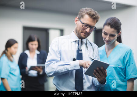 Doctor and nurse discussing over digital tablet - Stock Photo