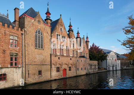 Red brick canal side buildings on the Groenerie canal, . Building on the left is part of the Oude Civiele Griffie - Stock Photo