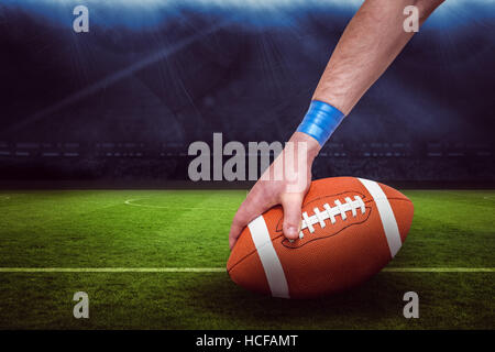 Composite image of american football player placing the ball 3D - Stock Photo