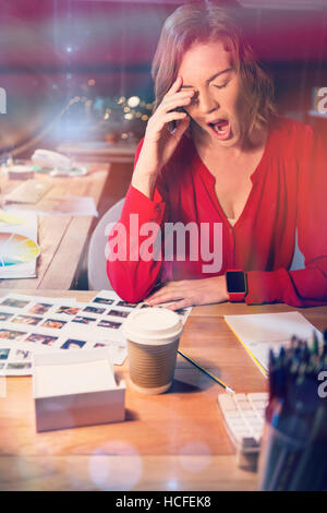 Stressed businesswoman yawning at desk - Stock Photo