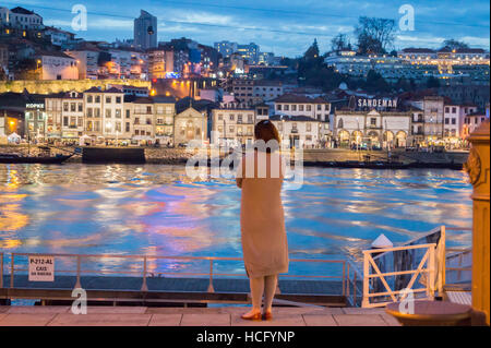 Lone figure of a woman on the Ribeira looking at the port lodges, Vila Nova de Gaia, River Douro, Porto, Portugal, - Stock Photo