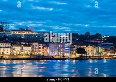 Port lodges, Vila Nova de Gaia, River Douro, Porto, Portugal, at dusk seen from the Ribeira - Stock Photo