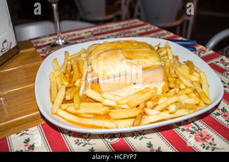 'Francesinha' steak, chorizo sausage and cheese toasted sandwich with savoury sauce, served with chips, Ribeira, - Stock Photo
