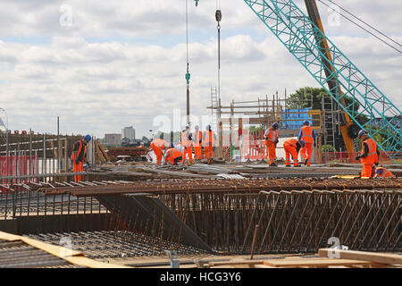 A reinforced concrete railway bridge under construction in Bermondsey, South London, UK. Workers prepare steelwork - Stock Photo