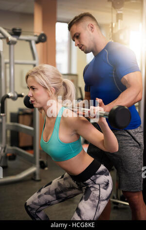 Woman doing difficult squat exercising - Stock Photo