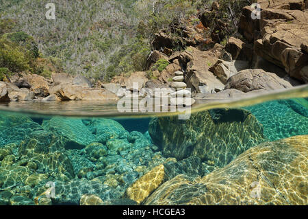 Over and under water in river with rocks on the riverbed underwater and a stack of pebbles above surface, Dumbea, - Stock Photo